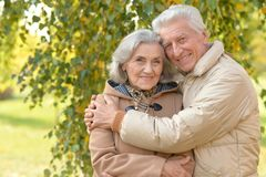 Happy senior couple in autumn park hugging. Senior couple hugging in park Royalty Free Stock Image