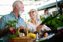 Happy senior couple with basket at the local market royalty free stock image
