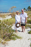 Happy senior couple beach vacation. An elderly couple walking hand in hand at the beach royalty free stock photos