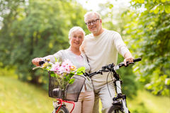 Happy senior couple with bicycles at summer park Royalty Free Stock Images