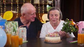 Happy senior couple blowing candles at birthday party stock video