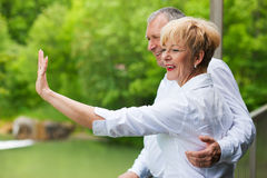 Happy senior couple on bridge waving hands Royalty Free Stock Photos