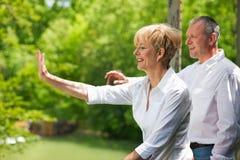 Happy senior couple on bridge waving hands Stock Photos