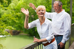 Happy senior couple on bridge waving hands Stock Photo