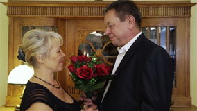 Happy senior couple with bunch of flowers at home celebrating their anniversary. Middle-aged man giving woman bouquet of red roses stock video