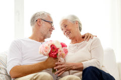 Happy senior couple with bunch of flowers at home Stock Photos