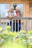 Happy senior couple in cabin enjoying. Senior couple standing oustide log cabin in countryside Stock Images