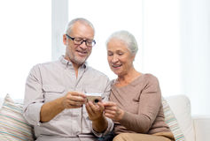 Happy senior couple with camera at home Stock Images