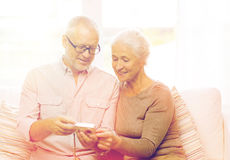 Happy senior couple with camera at home Royalty Free Stock Images