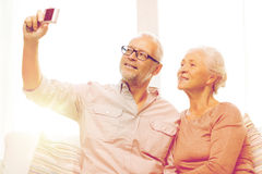Happy senior couple with camera at home Royalty Free Stock Photography