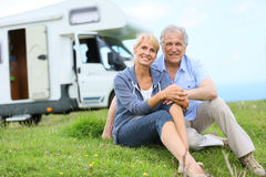 Happy senior couple camping with camping car Royalty Free Stock Image