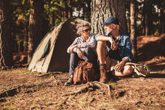 Happy senior couple camping in forest Royalty Free Stock Image