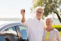 Happy senior couple with car key at seaside Stock Images