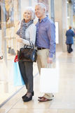 Happy Senior Couple Carrying Bags In Shopping Mall Stock Images