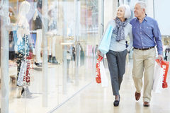 Happy Senior Couple Carrying Bags In Shopping Mall Royalty Free Stock Images