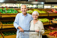 Happy senior couple with cart. At the grocery shop Royalty Free Stock Image
