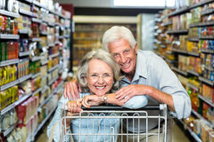 Happy senior couple with cart. Smiling at the camera Royalty Free Stock Photo