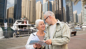 Happy senior couple with city map over harbor Royalty Free Stock Images