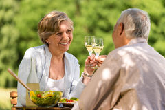 Happy senior couple clinking glasses. In garden Stock Photo