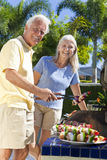 Happy Senior Couple Cooking on A Summer Barbecue. Happy senior man and woman couple outside cooking kebabs on a summer barbecue Royalty Free Stock Photography