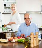 Happy senior couple cooking at their kitchen Royalty Free Stock Photo