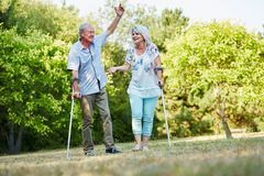 Happy senior couple on crutches in the park. Happy senior couple on crutches having fun in the park in summer Stock Photos