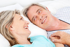 Happy senior couple cuddling in bed royalty free stock photos