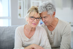 Happy senior couple cuddling at home Stock Image