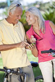 Happy Senior Couple Cycling Using Smart Phone GPS Stock Image