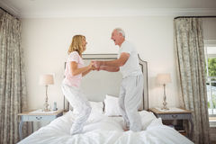 Happy senior couple dancing on bed. In bedroom royalty free stock photo