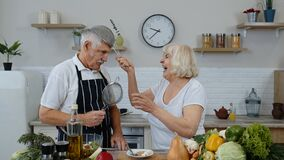 Happy senior couple dancing while cooking together in kitchen with fresh vegetables and fruits