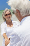 Happy Senior Couple Dancing Holding Hands on Beach Royalty Free Stock Images