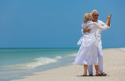 Happy Senior Couple Dancing Holding Hands on A Tropical Beach Royalty Free Stock Image