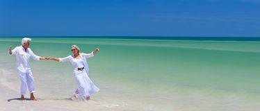 Happy Senior Couple Dancing Holding Hands on A Tropical Beach. Panoramic web banner happy senior men and women couple dancing and holding hands on a deserted royalty free stock image