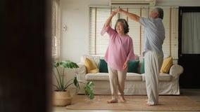 Happy senior couple dancing at home.