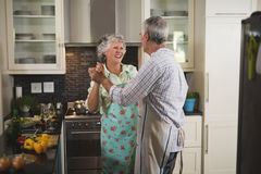 Happy senior couple dancing in kitchen stock image