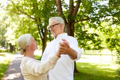 Happy senior couple dancing at summer city park stock photos