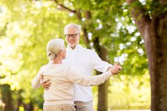 Happy senior couple dancing at summer park stock photo