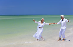 Happy Senior Couple Dancing on Tropical Beach. Happy senior man and woman couple dancing and holding hands on a deserted tropical beach with bright clear blue Royalty Free Stock Photos