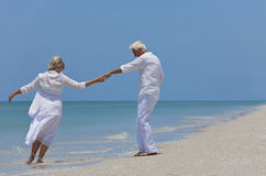 Happy Senior Couple Dancing on A Tropical Beach. Happy senior man and woman couple dancing and holding hands on a deserted tropical beach with bright clear blue Royalty Free Stock Photography