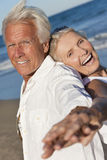 Happy Senior Couple Dancing on A Tropical Beach. Happy senior men and women couple dancing having fun back to back on a deserted tropical beach Stock Photography