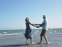 Happy Senior Couple Dancing On Tropical Beach. Full length of happy senior couple holding hands and dancing on tropical beach Stock Photo