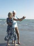 Happy Senior Couple Dancing On Tropical Beach stock photography