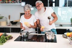 Free Happy Senior Couple Dancing While Cooking Together At Home - Mature People Having Fun Preparing The Lunch - Joyful Elderly Stock Photo - 188770390