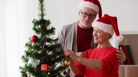 Happy senior couple decorating christmas tree stock video footage