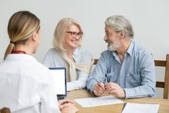Happy senior couple discussing house purchase at meeting with ag royalty free stock images