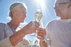 Happy senior couple drinking champagne outdoors. Family, age, holidays, leisure and people concept - close up of happy senior couple clinking champagne glasses Royalty Free Stock Photos