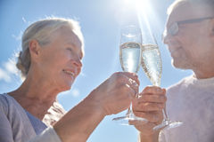Happy senior couple drinking champagne outdoors. Family, age, holidays, leisure and people concept - close up of happy senior couple clinking champagne glasses Stock Images