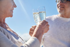 Happy senior couple drinking champagne outdoors. Family, age, holidays, leisure and people concept - close up of happy senior couple clinking champagne glasses Stock Photography