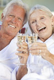 Happy Senior Couple Drinking Champagne White Wine. Happy senior men and women couple sitting together outside in sunshine wearing white bathrobes celebrating Stock Photography